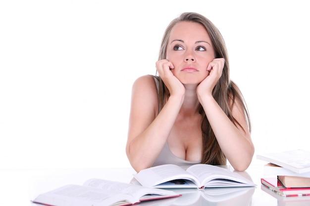 Myśląca studencka kobieta przy biurkiem