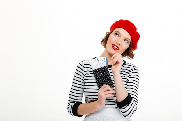 Myśląca turystyczna dama trzyma paszport z biletami