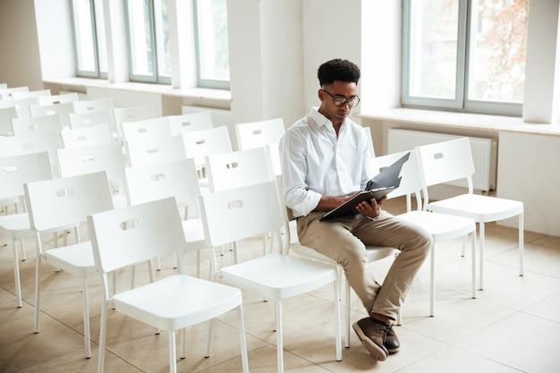 Myślący afrykański mężczyzna siedzi coworking z schowkiem