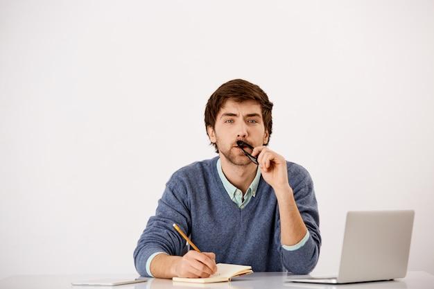 Myślący biznesmen siedzący przy biurku, piszący, próbujący wymyślony pomysł, mrużący oczy, zastanawiając się nad nową treścią