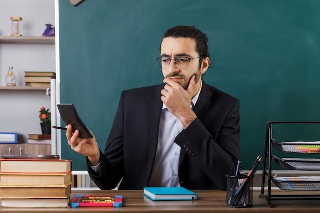Myślący chwycił podbródek nauczyciel w okularach, trzymając i patrząc na kalkulator siedzący przy stole z szkolnymi narzędziami w klasie