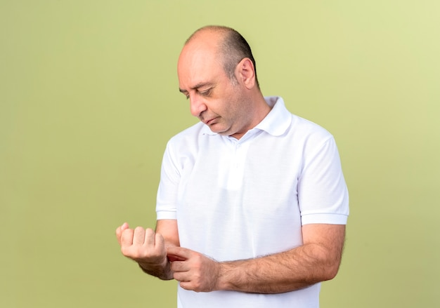Myślący dojrzały mężczyzna patrząc i kładąc rękę na nadgarstku na białym tle na oliwkowej ścianie