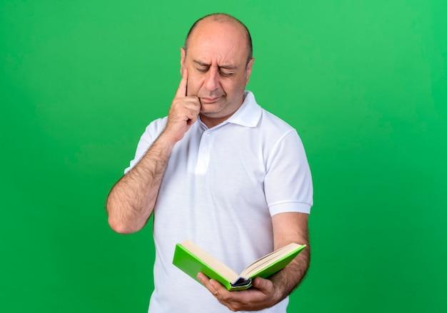 Myślący dorywczo dojrzały mężczyzna trzyma i patrząc na książkę na białym tle na zielonej ścianie