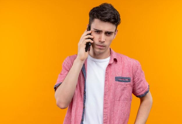 Myślący kaukaski młody facet ubrany w różową koszulę mówi przez telefon na odizolowanej pomarańczowej ścianie