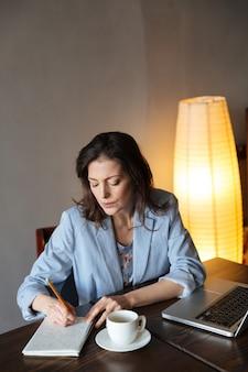 Myślący kobieta pisarz siedzi w domu