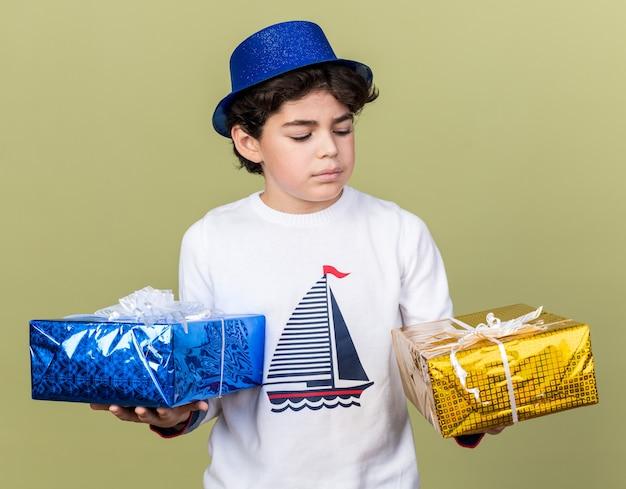 Myślący mały chłopiec w niebieskiej imprezowej czapce, trzymający i patrzący na pudełka z prezentami