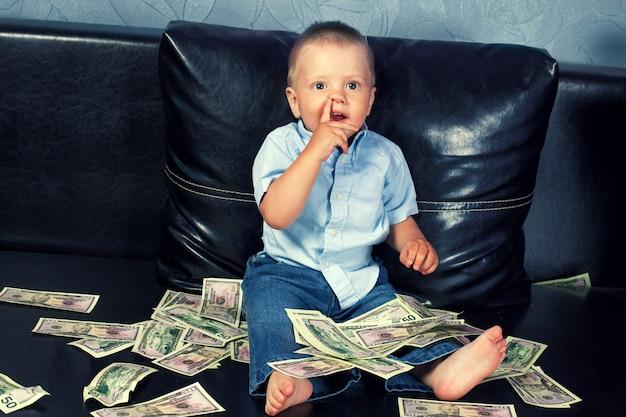 Myślący mały chłopiec z fałszywymi pieniędzmi