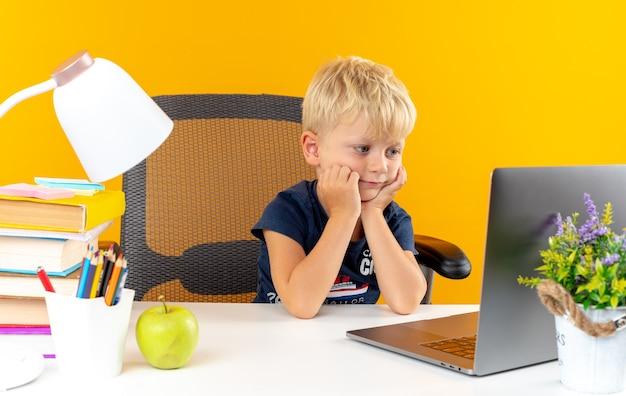 Myślący mały szkolny chłopiec siedzi przy stole z szkolnymi narzędziami, patrząc na laptopa, kładąc ręce na policzkach