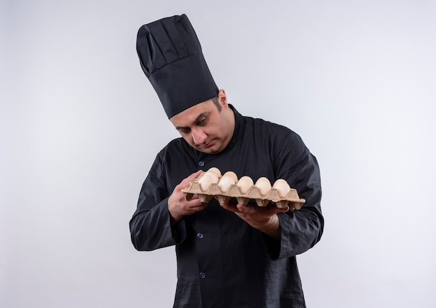 Myślący mężczyzna w średnim wieku kucharz w mundurze szefa kuchni patrząc na partię jaj w ręku