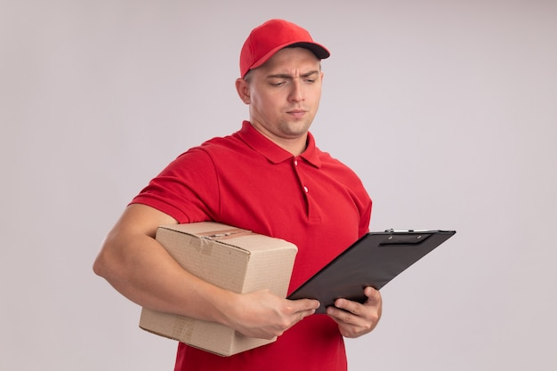 Myślący młody dostawca w mundurze z czapką trzymającą pudełko i patrzący na schowek w dłoni na białym tle na białej ścianie