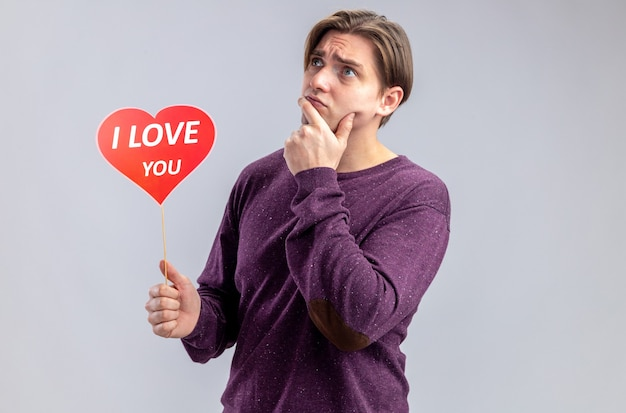 Myślący młody facet na walentynki trzymając czerwone serce na patyku z tekstem kocham cię kładąc rękę na brodzie na białym tle