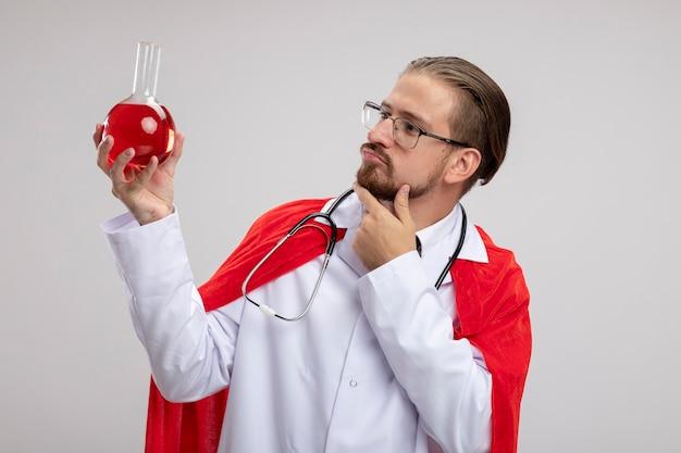 Myślący młody facet superbohatera w szlafroku medycznym ze stetoskopem i okularami, trzymając i patrząc na szklaną butelkę chemii wypełnioną czerwonym płynem, kładąc dłoń na brodzie na białym tle