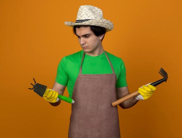 Myślący młody męski ogrodnik w mundurze w kapeluszu ogrodniczym z rękawiczkami trzymający i patrząc na motykę grabie z grabiami na pomarańczowej ścianie