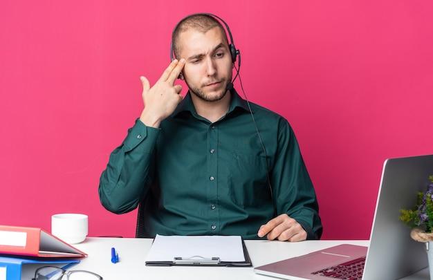 Myślący młody mężczyzna operator call center noszący zestaw słuchawkowy siedzący przy biurku z narzędziami biurowymi, patrzący na laptopa pokazujący gest samobójczy z gestem pistoletu