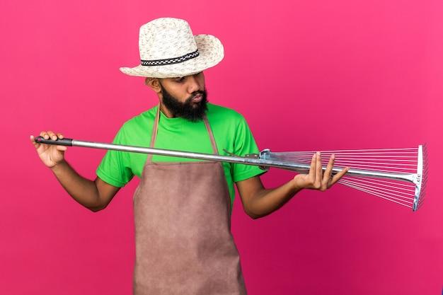 Myślący młody ogrodnik afro-amerykański facet w kapeluszu ogrodniczym, trzymający i patrzący na grabie do liści odizolowanych na różowej ścianie