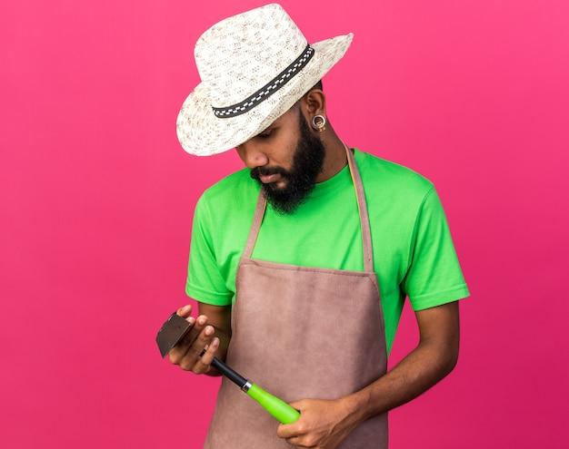 Myślący młody ogrodnik afro-amerykański facet w kapeluszu ogrodniczym, trzymający i patrzący na grabie motyki izolowane na różowej ścianie