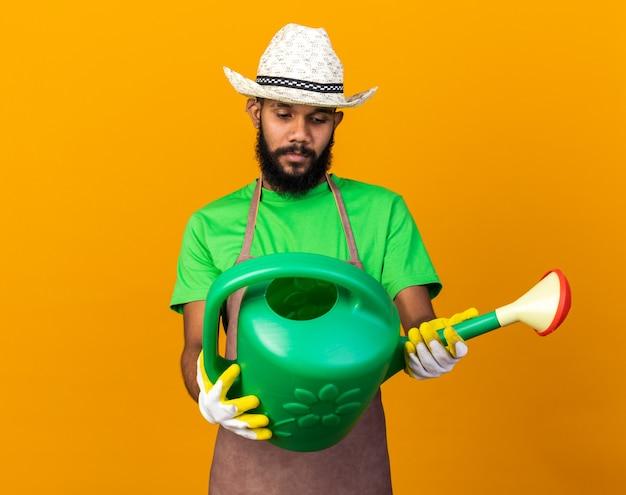 Myślący młody ogrodnik afroamerykański facet w kapeluszu ogrodniczym i rękawiczkach, trzymający i patrzący na konewkę