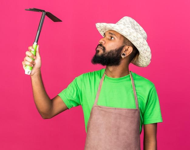 Myślący młody ogrodnik afroamerykański facet w kapeluszu ogrodniczym, trzymający i patrzący na grabie motyki