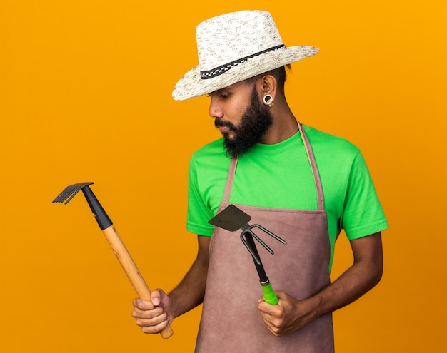 Myślący młody ogrodnik afroamerykański facet w kapeluszu ogrodniczym, trzymający i patrzący na grabie z motyką