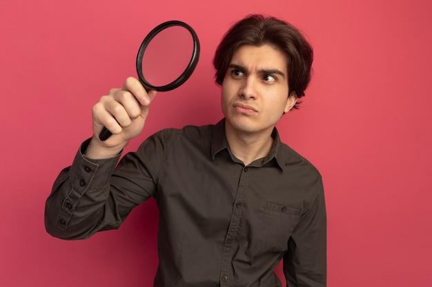 Myślący młody przystojny facet na sobie czarną koszulkę, trzymając i patrząc na lupę na białym tle na różowej ścianie