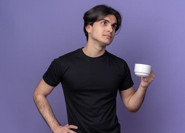 Myślący młody przystojny facet ubrany w czarny t-shirt, trzymając filiżankę kawy, kładąc rękę na biodrze na białym tle na fioletowej ścianie