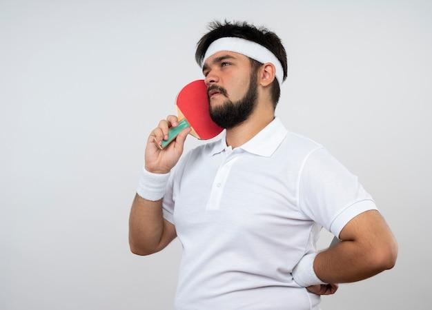 Myślący młody sportowy mężczyzna patrząc z boku z opaską na głowę i opaską na rękę trzyma rakietę do ping-ponga na policzku kładąc rękę na biodrze odizolowaną na białej ścianie
