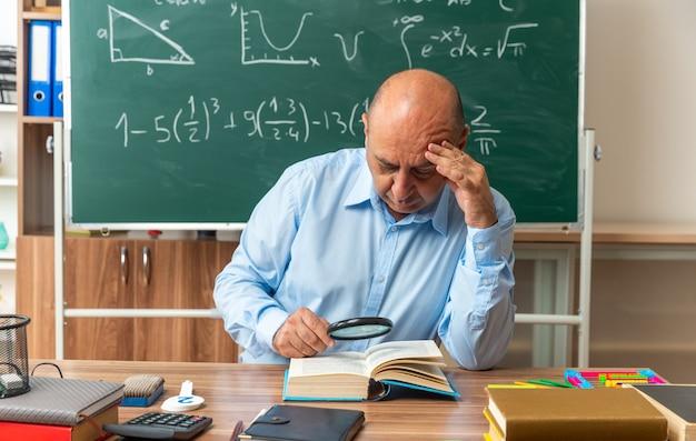 Myślący nauczyciel w średnim wieku siedzi przy stole z przyborami szkolnymi, czytając książkę z lupą, kładąc rękę na czole w klasie