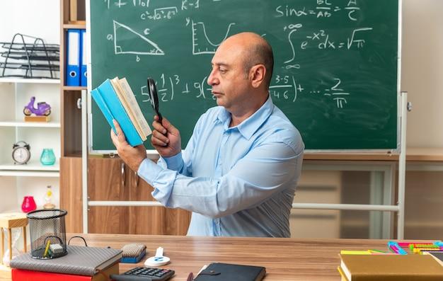 Myślący nauczyciel w średnim wieku siedzi przy stole z przyborami szkolnymi, czytając książkę z lupą w klasie