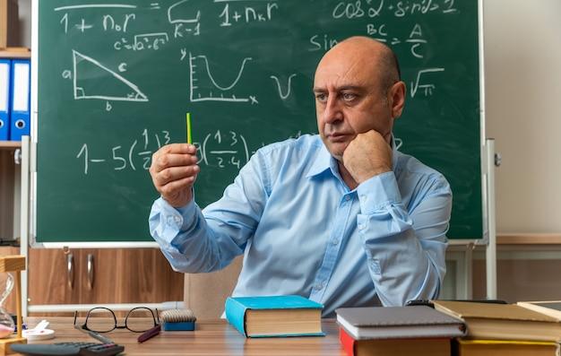 Myślący nauczyciel w średnim wieku siedzi przy stole z przyborami szkolnymi trzymając i patrząc na ołówek w klasie