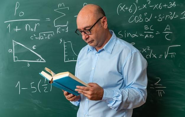 Myślący nauczyciel w średnim wieku w okularach, stojący przed tablicą, czytając książkę