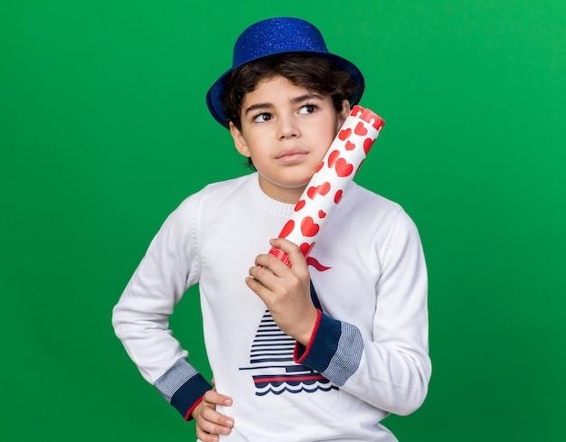 Myślący patrząc z boku mały chłopiec w niebieskiej imprezowej czapce, trzymający armatę konfetti, kładąc rękę na biodrze na białym tle na zielonej ścianie