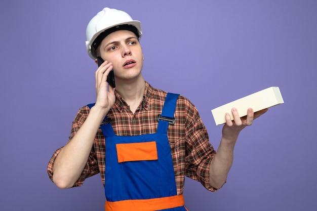 Myślący patrząc z boku młody mężczyzna budowniczy ubrany w mundur trzymający cegłę mówi przez telefon
