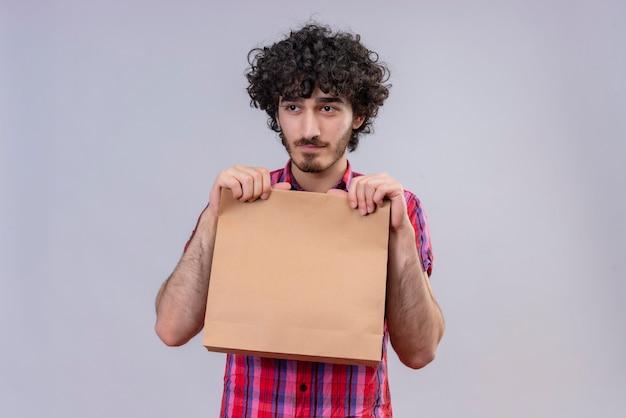 Myślący przystojny mężczyzna z kręconymi włosami w kraciastej koszuli, trzymając torbę na zakupy, patrząc z boku