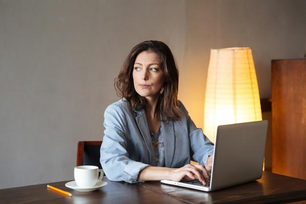 Myślący skoncentrowany kobieta pisarz siedzi indoors używać laptop