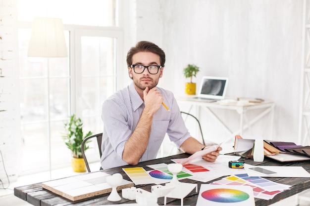 Myślący. zamyślony brodaty mężczyzna siedzi przy stole i trzyma kartkę papieru i ołówek