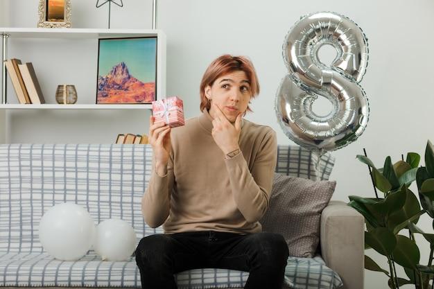 Myślenie chwycił podbródek przystojny facet na szczęśliwy dzień kobiet trzymając prezent siedzący na kanapie w salonie