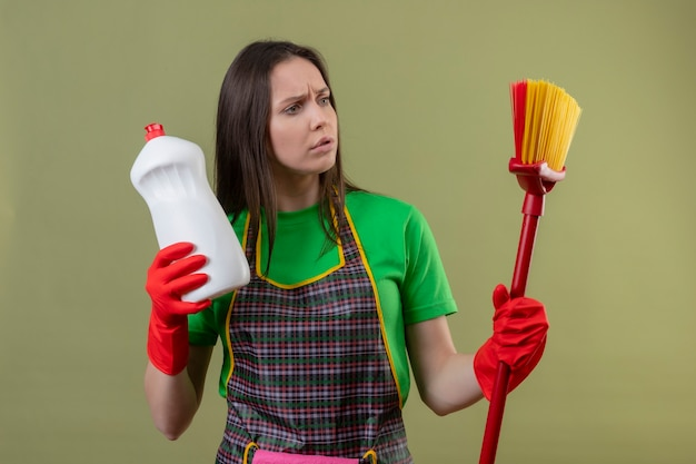 Myślenie czyszczenia młoda dziewczyna ubrana w mundur w czerwonych rękawiczkach, trzymając środek czyszczący, patrząc na mopa na dłoni na odizolowanej zielonej ścianie