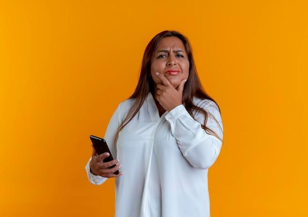 Myślenie dorywczo kaukaski kobieta w średnim wieku trzymając telefon i kładąc rękę pod brodą na białym tle na żółtej ścianie