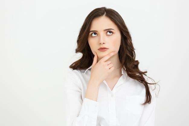 Myślenie kaukaski kobieta biznesu z ręką na brodzie i patrząc w górę