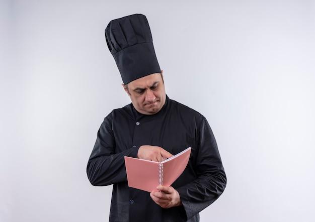 Myślenie kucharza w średnim wieku mężczyzna w mundurze szefa kuchni czyta coś na notebooku w ręku