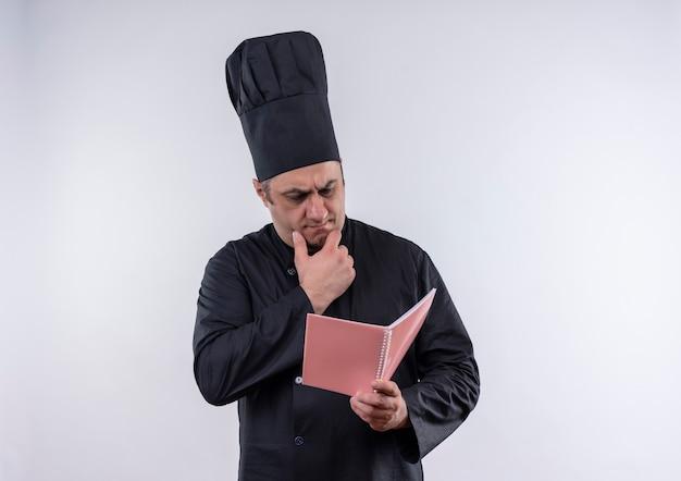Myślenie kucharza w średnim wieku mężczyzna w mundurze szefa kuchni patrząc na notatnik w ręku