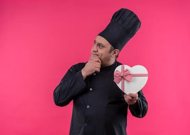 Myślenie kucharza w średnim wieku mężczyzna w mundurze szefa kuchni, trzymając pudełko w kształcie serca z miejsca na kopię