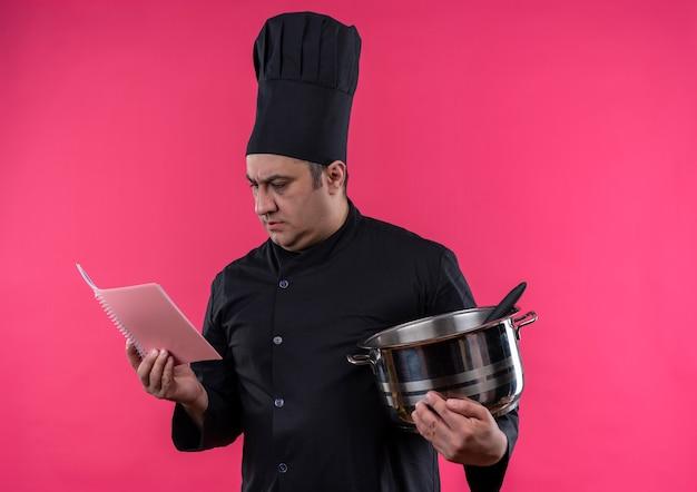Myślenie kucharza w średnim wieku mężczyzna w mundurze szefa kuchni trzymając rondel patrząc na notatnik w ręku