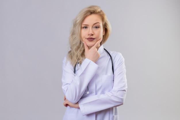 Myślenie lekarza młoda dziewczyna ubrana w stetoskop w sukni medycznej położyła rękę na szczęce na białym tle