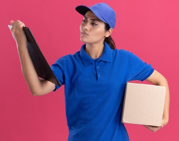 Myślenie młoda dziewczyna dostawy ubrana w mundur z czapką, trzymając pudełko i patrząc na schowek w ręku na białym tle na różowej ścianie