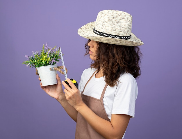 Myślenie młoda kobieta ogrodnik w mundurze na sobie kapelusz ogrodniczy pomiarowy kwiat w doniczce z centymetrem