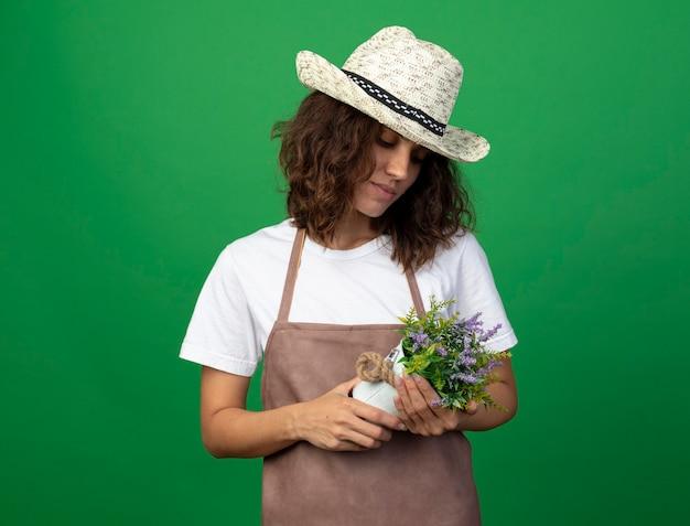 Myślenie młoda kobieta ogrodnik w mundurze na sobie kapelusz ogrodniczy, trzymając i patrząc na kwiat w doniczce