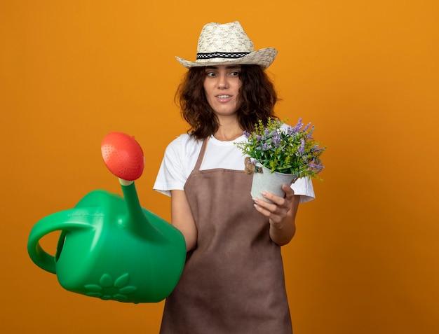 Myślenie młoda kobieta ogrodnik w mundurze na sobie kapelusz ogrodniczy trzymając konewkę i patrząc na kwiat w doniczce w dłoni