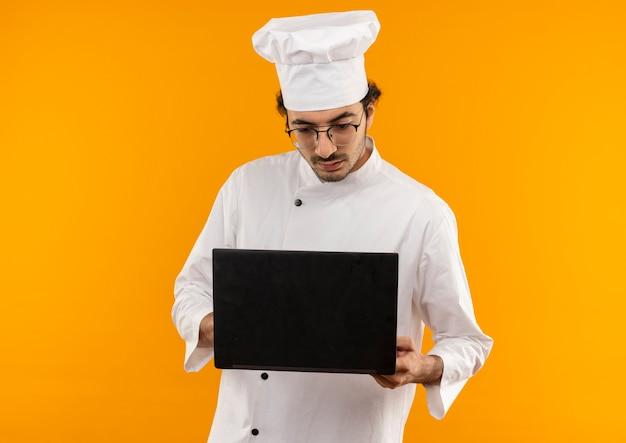 Myślenie młody mężczyzna kucharz ubrany w mundur szefa kuchni i okulary, trzymając i patrząc na laptopa na białym tle na żółtej ścianie
