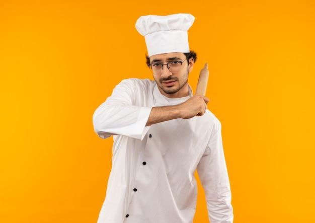 Myślenie młody mężczyzna kucharz ubrany w mundur szefa kuchni i okulary trzymając wałek do ciasta wokół ramienia na białym tle na żółtej ścianie